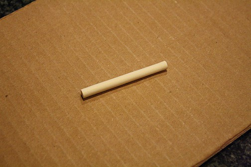 piece of wood dowel on top of cardboard