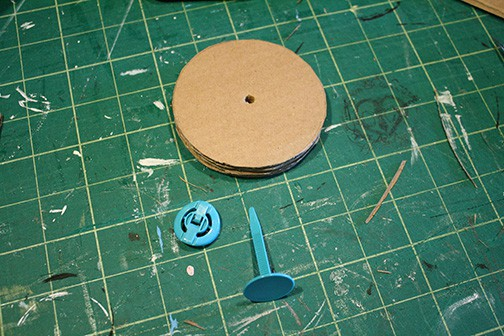 round cardboard circles with hole in the middle and blue fastener
