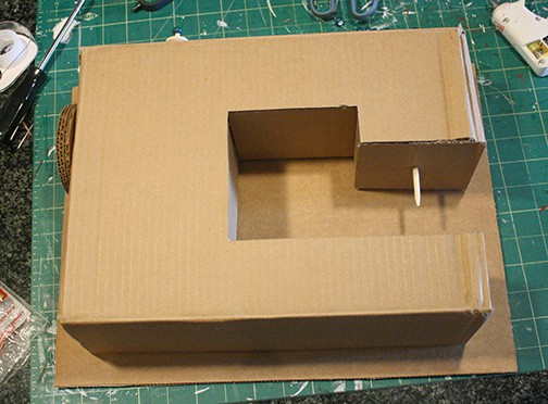 sewing machine laying on top of another piece of cardboard to trace the back side