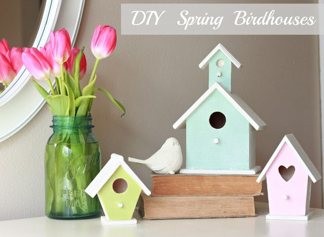 cute pastel birdhouses on a tabletop with a vase of pink tulips
