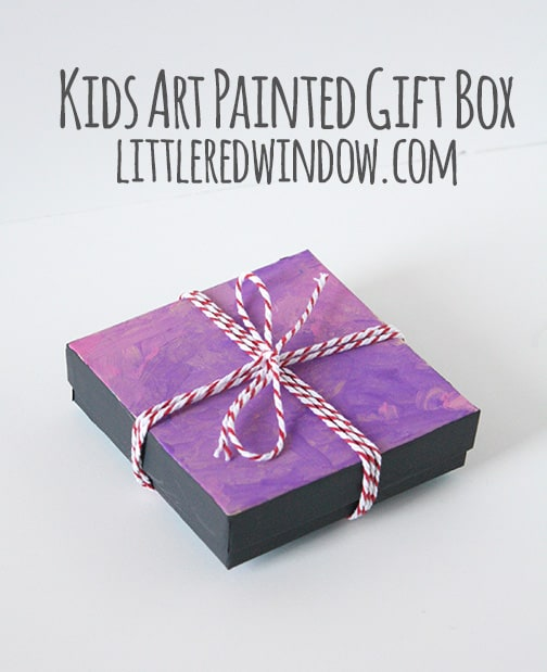 gift box with pink and purple swirly painted lid tied with red baker's twine bow