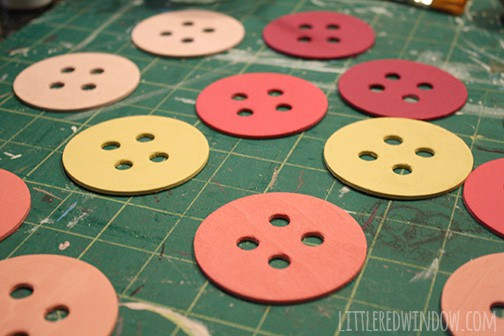 Wood button shapes painted in shades of pink and yellow