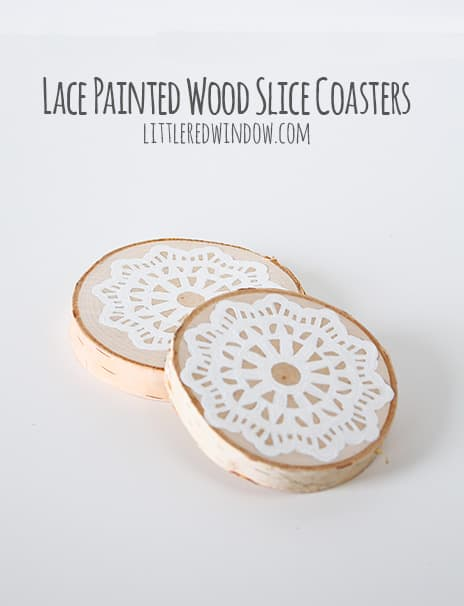 Finished wood slice coasters with painted lace pattern on top in front of a white background