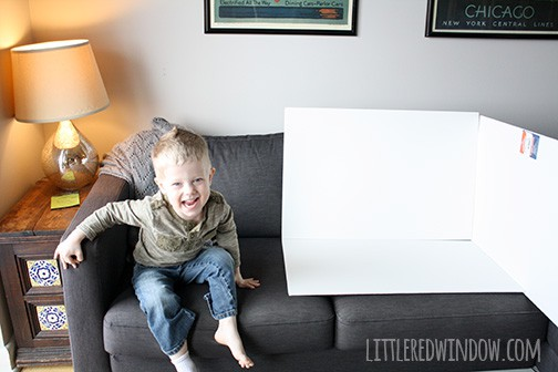 little boy sitting on a gray couch next to propped up white foam boards for photo taking