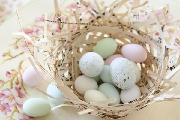 bird's nest made of strips of paper with small pastel eggs inside