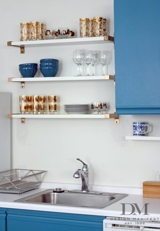 kitchen with blue cabinets and white shelves with gold brackets