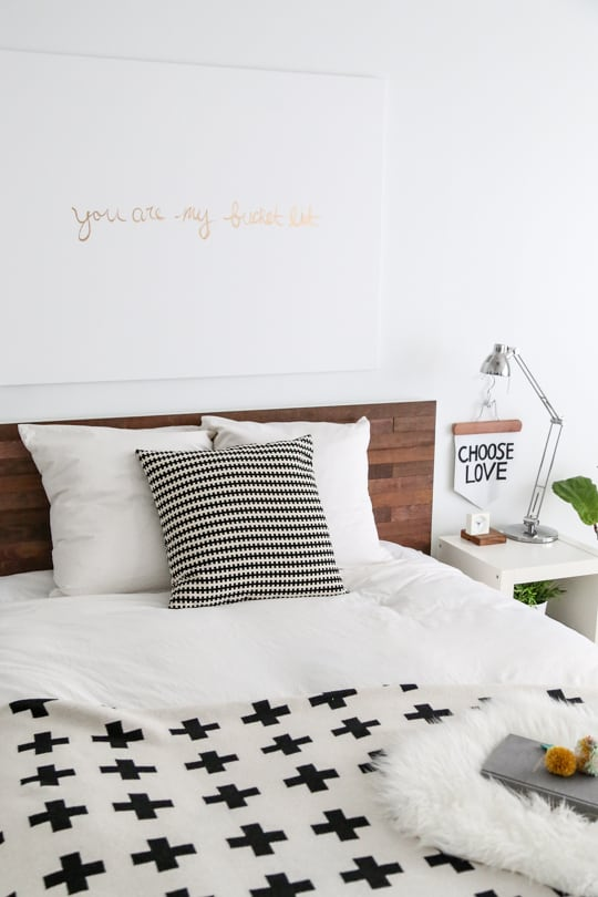 wood slat headboard in a black and white decorated bedroom