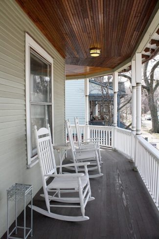 view of a porch with three white rocking chairs on it