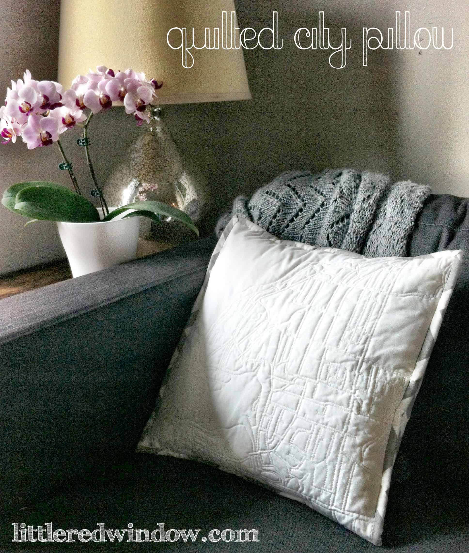 Quilted city pillow in the corner of a couch next to a lamp and orchid