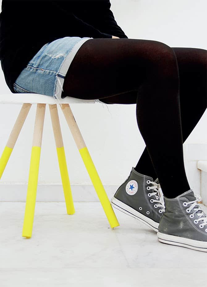 Person wearing Converse sitting on a stool with 4 legs dipped in yellow paint