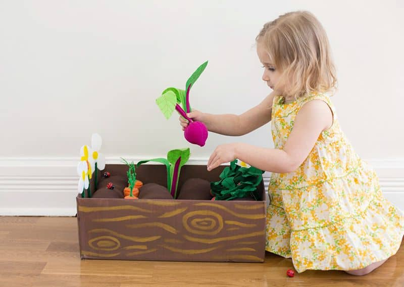 Little girl playing with toy garden set