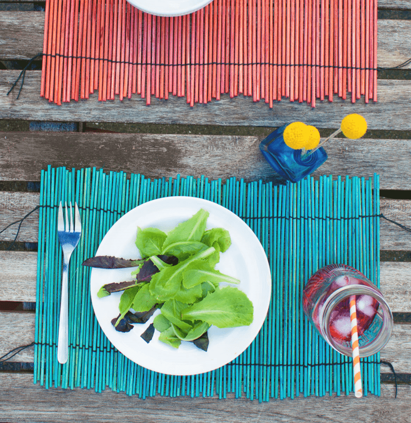 Overhead view of blue and red bamboo placemats with place setting on them
