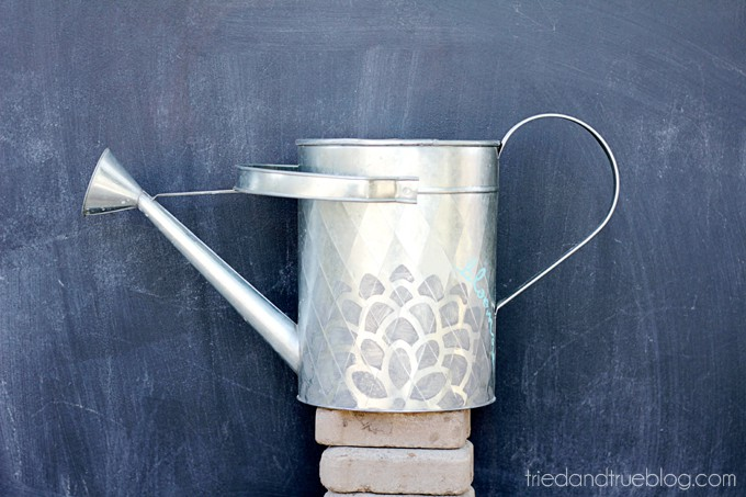 Silver watering can with a flower pattern on the side
