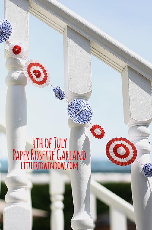Red and white rosettes strung on baker's twine and hanging along a white railing outside
