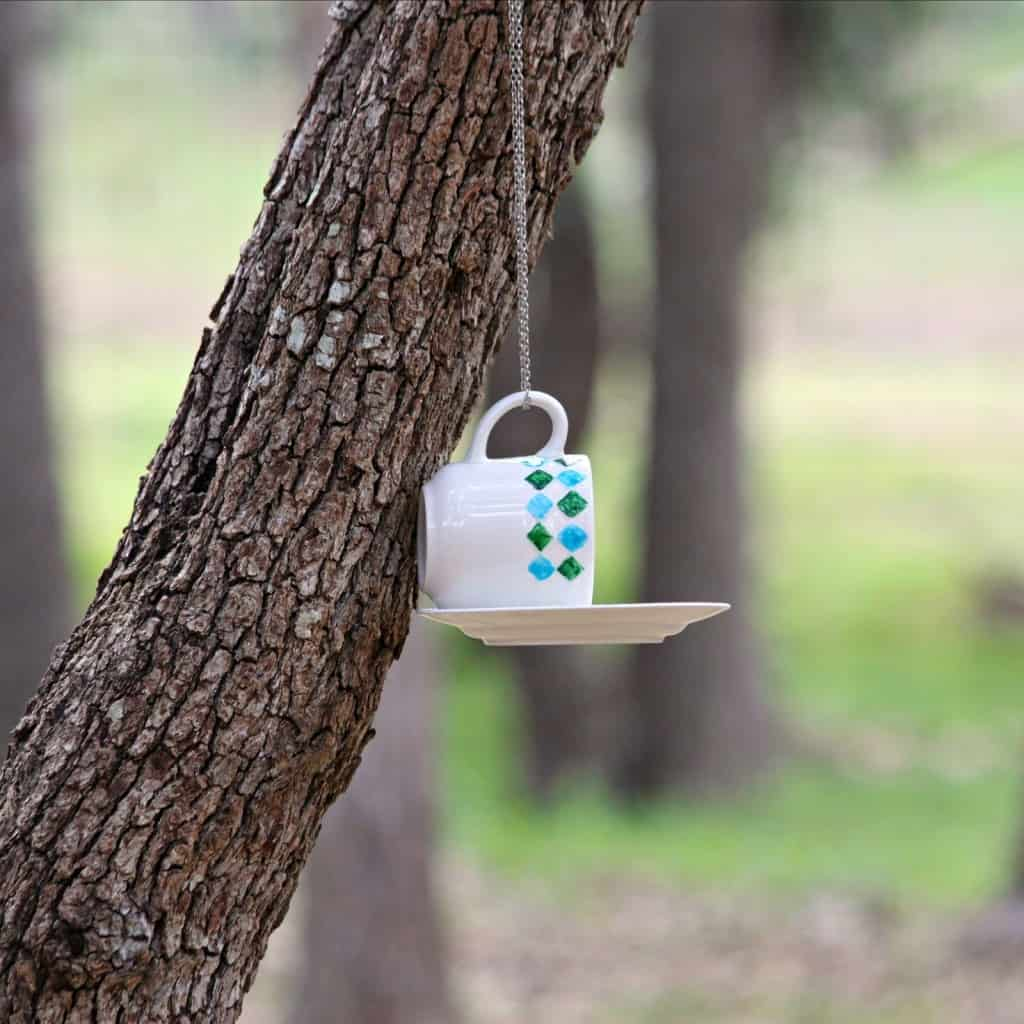 Bird feeder made from a teacup and saucer hanging from a tree