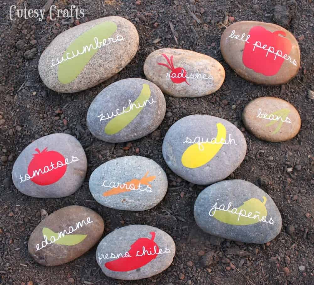 Rocks painted with silhouettes of vegetable shapes and the name of the vegetable written on top