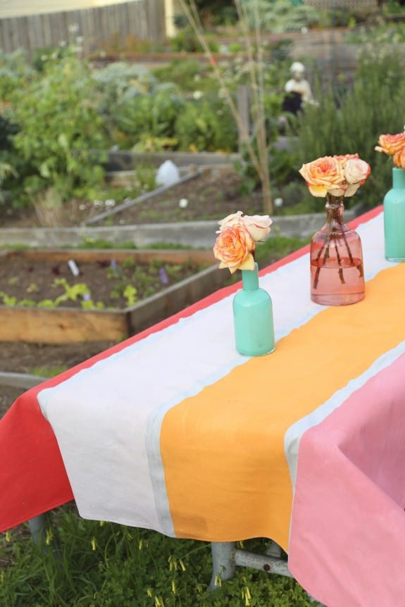 Red, orange and pink striped tablcloth on a table outside