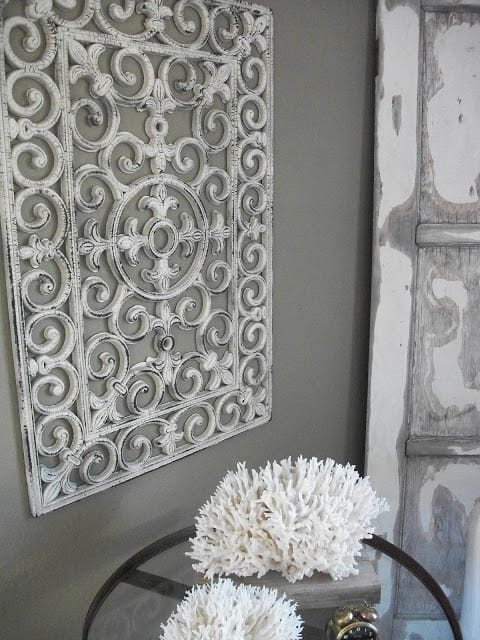 Gray wall with white metal looking decorative scroll gate