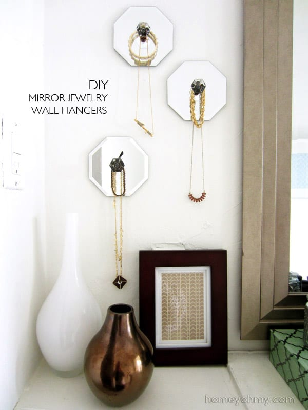 Hexagon mirrors with knobs in the center hanging on a wall to hold necklaces