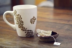 White mug with gold geometric pattern on it, next to a tea bag