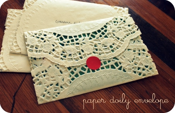 Envelope made from paper doily with red dot sticker sealing it