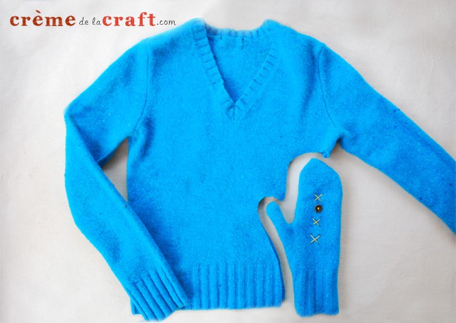 Blue sweater with a mitten shape cut out of the lower right