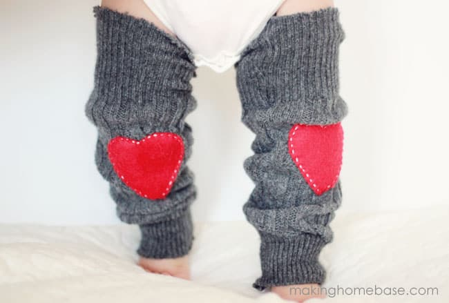 Baby's legs wearing sweater knit gray legwarmers with red felt hearts on the knees