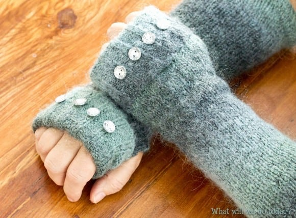 Person's hands wearing gray knit wristwarmers with 4 buttons across the knuckles of each