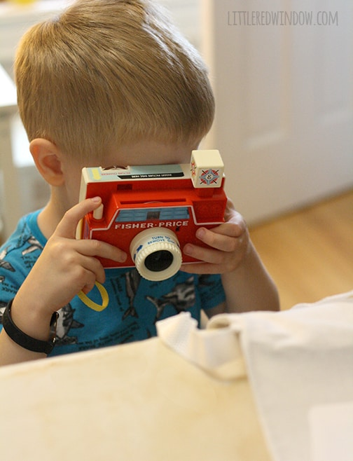 Little boy taking a picture with a toy camera