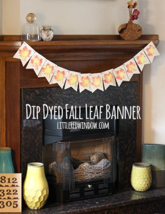 Finished banner with fanric pennants and wood leaves on top hanging across a fireplace mantel