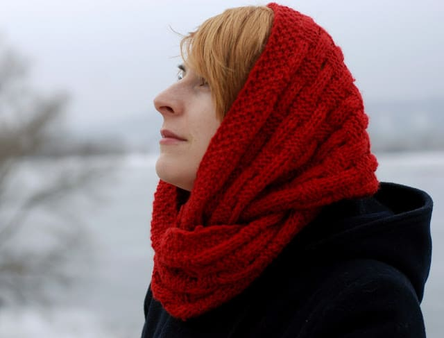 Woman wearing a red basketweave knit cowl over her head