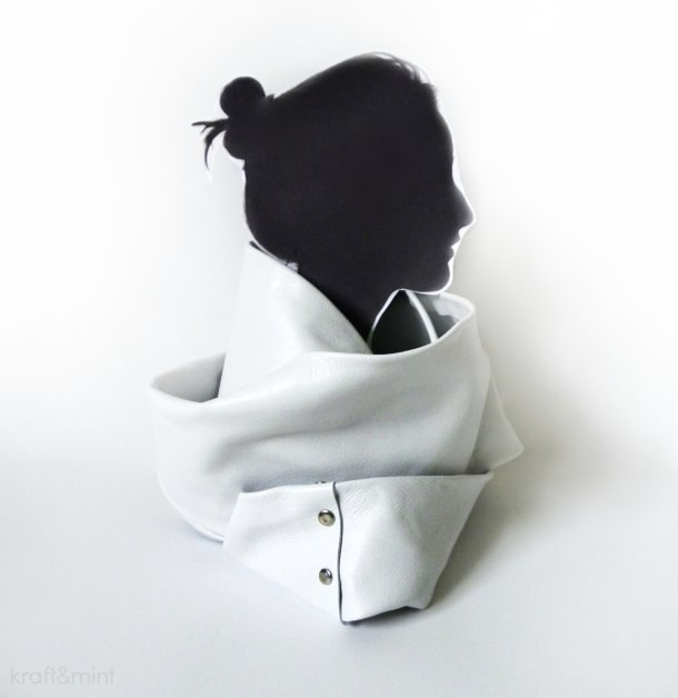 Flat woman silhouette wearing a white leather button up cowl