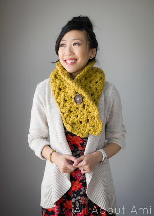 Woman smiling wearing a chunky yellow cowl with a big brown button