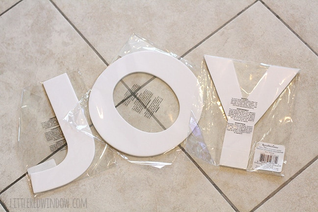 Three cardboard letters J O and Y