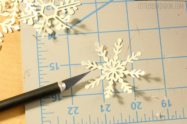 white paper snowflakes with a craft knife