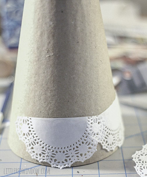 Paper mache cone being covered with doilies