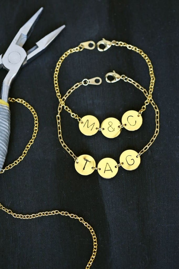 Two gold bracelets with circular tags with intiials stamped into them