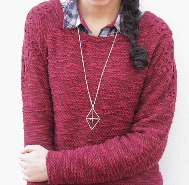 Woman in a red sweater with a long gold necklace with 3d geometric shape pendant