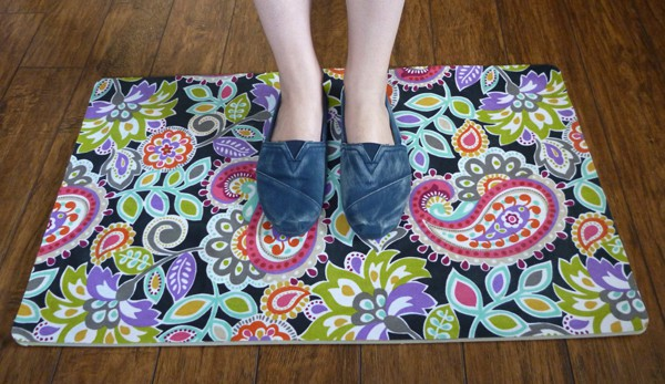 Woman in Toms shoes standing on a bright paisley doormat