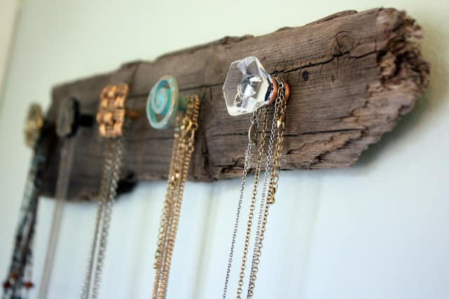 A piece of driftwood on the wall with decorative knobs added to hold necklaces