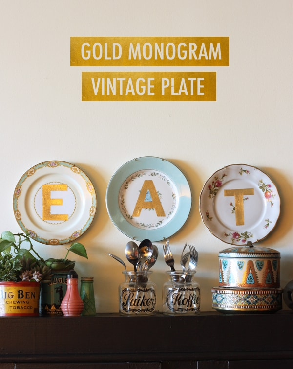 Kitchen wall with three mismatched china plates hanging on it, each with a big gold letter spelling EAT
