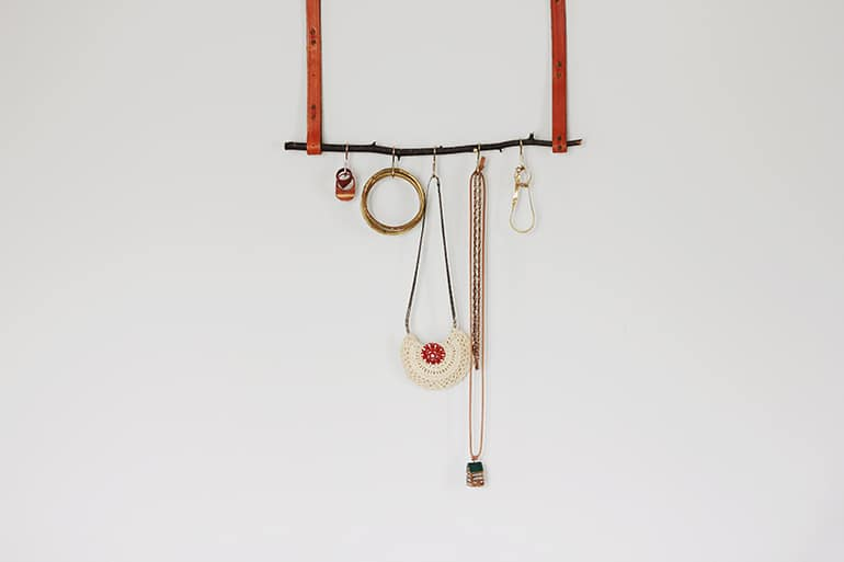 a tree branch hanging from leather straps with hooks to hold necklaces