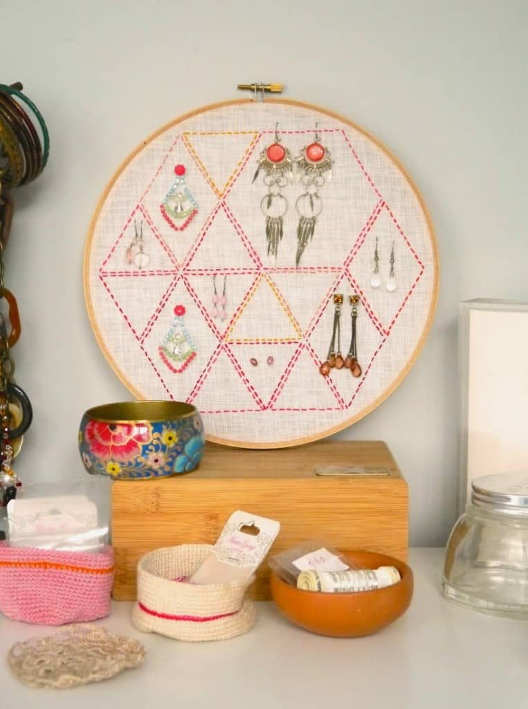 Embroidery hoop wth hexagon pattern and various earrings attached to it