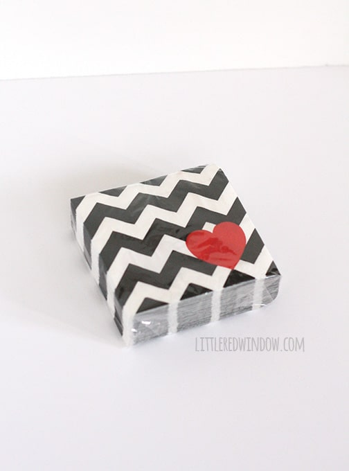 Package of black and white chevron paper napkins with a red heart in their lower right corners