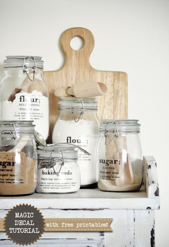 Group of 5 lidded glass jars with labels that have the written definition of each baking ingredient like flour and sugar
