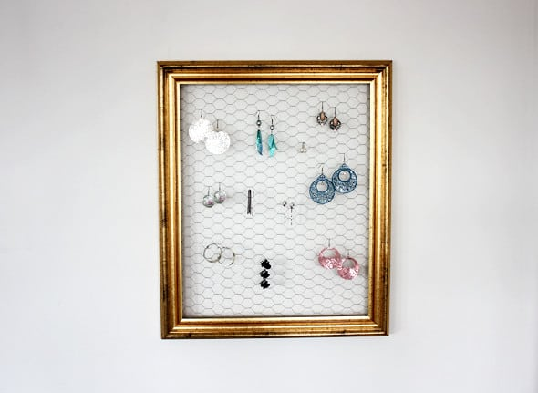 Picture frame filled with chicken wire with earrings hanging on it