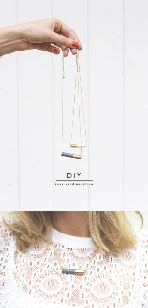 hand holding two necklaces with concrete pendants that are dipped half in gold