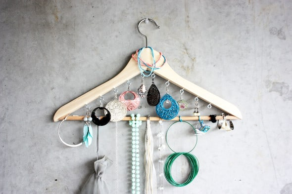 A wooden hanger with small hooks added to hold jewelry