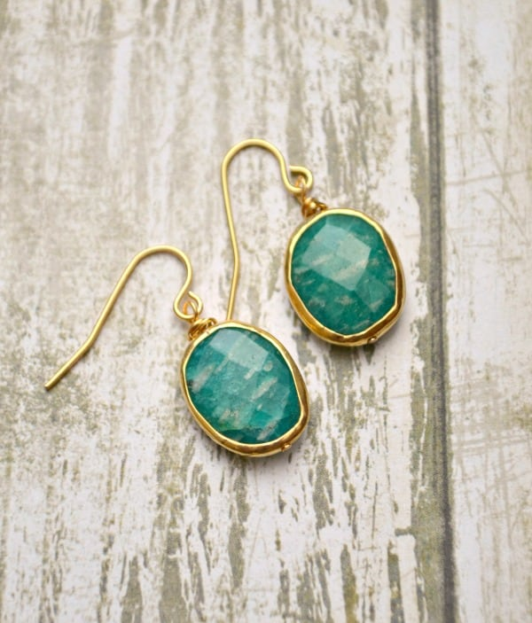 Gold drop earrings with faceted teal stones on a wood table