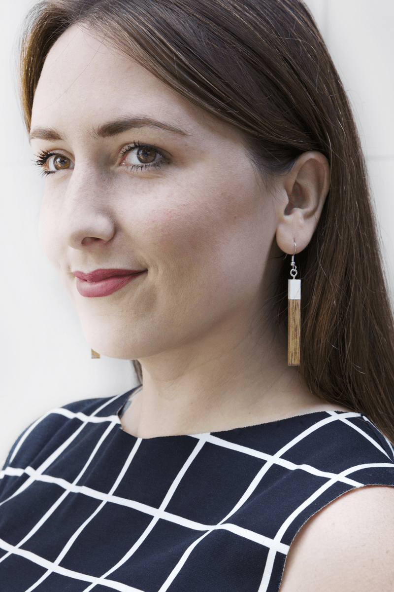 woman wearing earrings made from small rectangles of wood